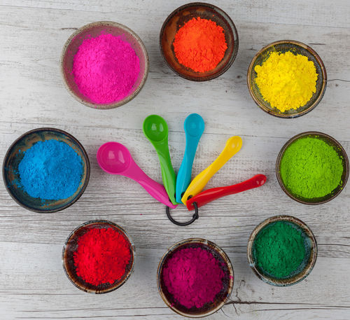 Vibrant colorful Holi powder in cups arranged in circle with measuring spoons. Top view Bowl Choice Close-up Day Happy Holi High Angle View Holi Holi Powder Multi Colored No People Powder Paint Red Table Top View Variation