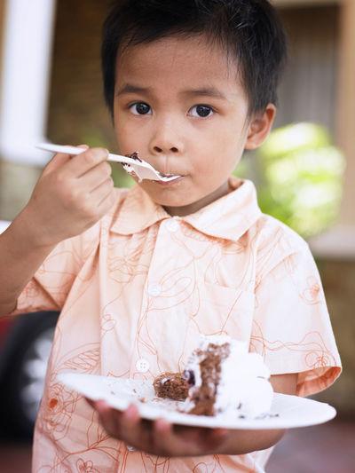 Close-Up Portrait Of Boy Eating Birthday Cake