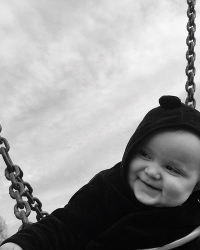 Close-up of happy baby boy looking away while sitting on swing