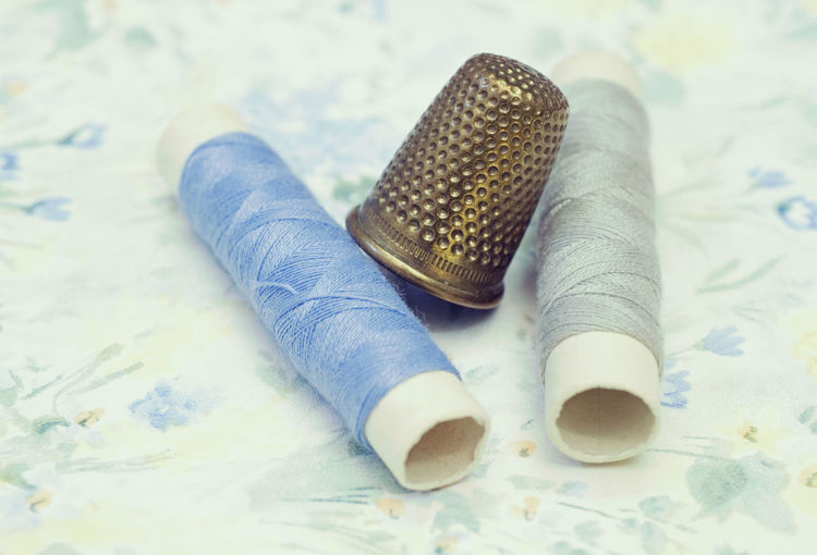 High angle view of thimble with threads on table