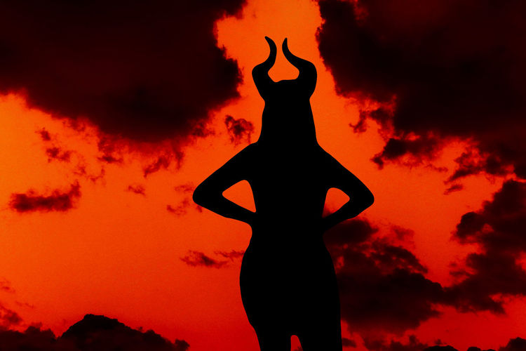 Silhouette woman with horns standing against orange sky
