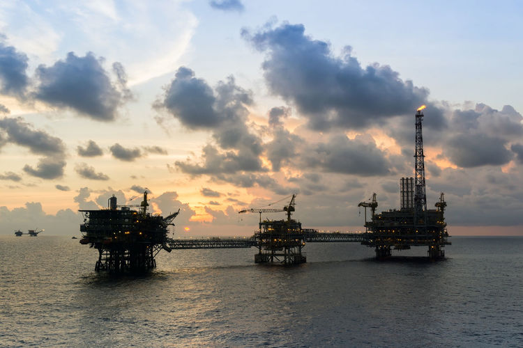 sunset at oil field Upstream Oil Rig Evening Oil Gas Oil And Gas Petroleum Silhouette Cloudy Ocean Horizon Over Water Wave Drilling Rig Oil Pump Offshore Platform Oil Industry Sea Water Nautical Vessel Business Finance And Industry Oil Field Fossil Fuel Oil Crude Oil Natural Gas