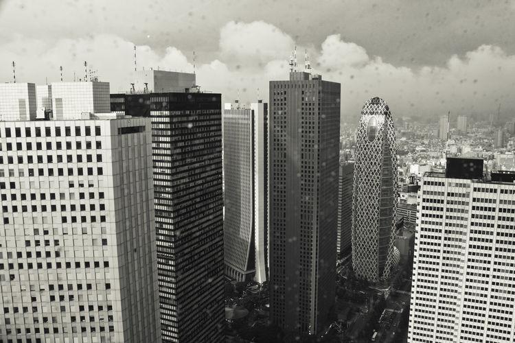 Modern buildings against sky in city seen through window