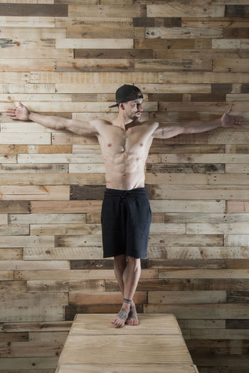 Full length of shirtless man standing against wooden wall
