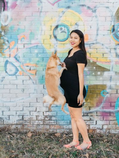 Portrait of pregnant woman with dog against brick wall