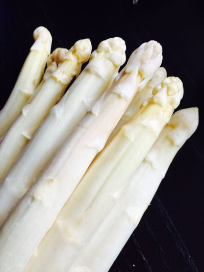 Close-up of white asparaguses against black background