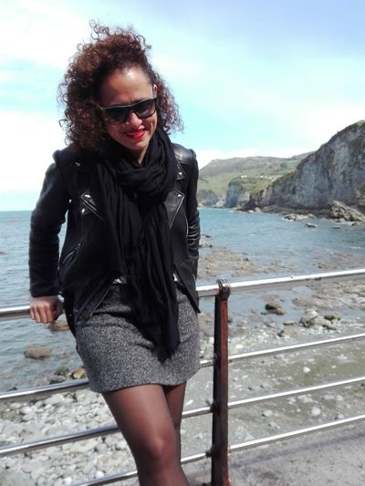 Portrait of woman wearing sunglasses while standing by railing against sea