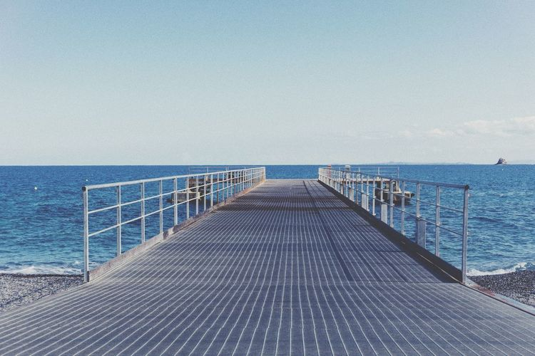 Empty pier over sea against clear sky