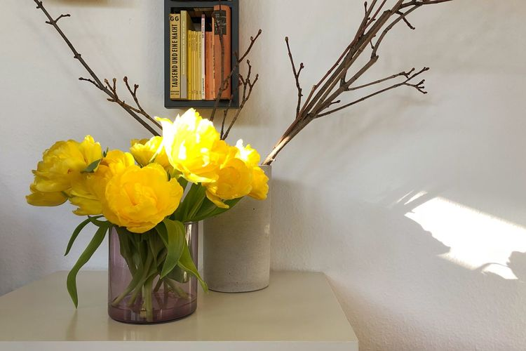 Close-up of yellow flower vase on table at home