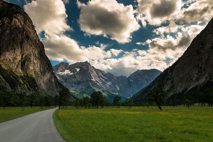 Road amidst grassy field leading towards mountains against sky