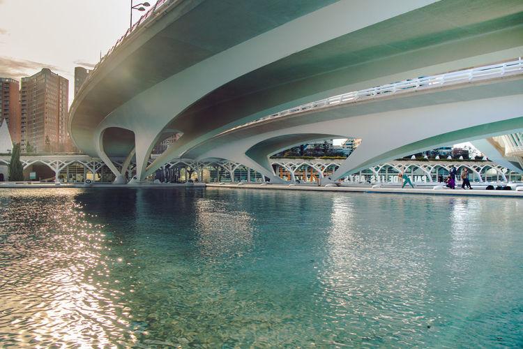 Illuminated bridge over river in city