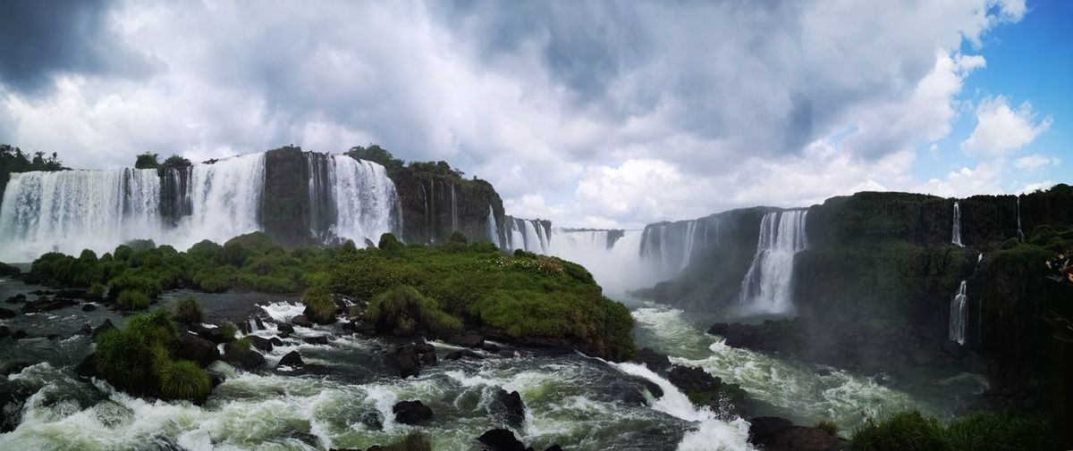 Panoramic view of iguazu waterfalls against cloudy sky