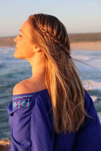 Beautiful woman looking at sea against sky