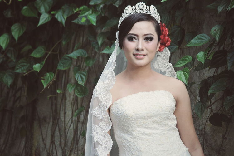 Bride Wearing Wedding Dress And Tiara While Standing Against Tree