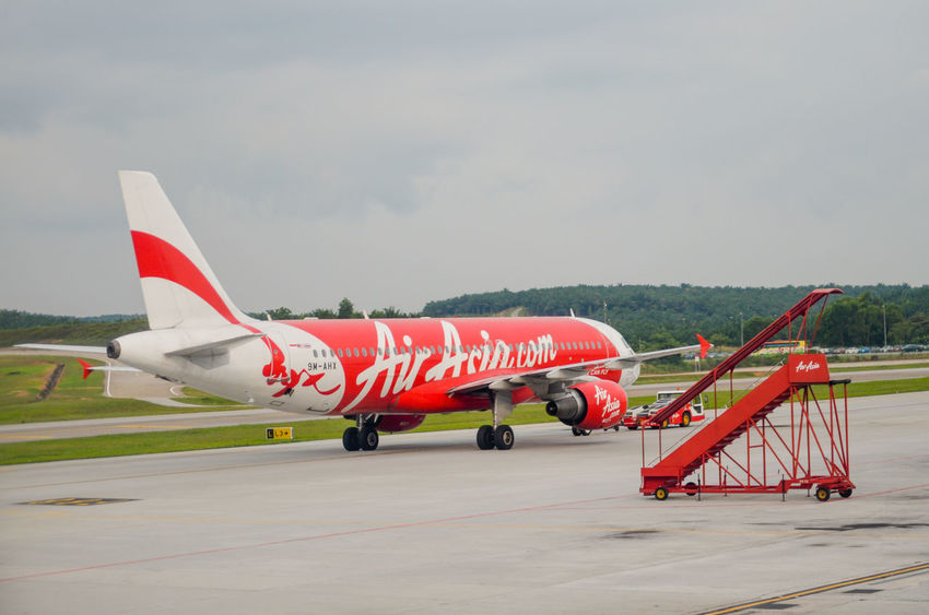 AirAsiaMalaysia AirAsiaThailand AirAsiaZest Airasiaindonesia Aerospace Industry Air Vehicle Airasia Airasia Malaysia Airasiax Airplane Airport Airport Runway Day Military Mode Of Transportation Nature No People Outdoors Plane Public Transportation Red Runway Side View Sky Stationary Text Transportation Travel