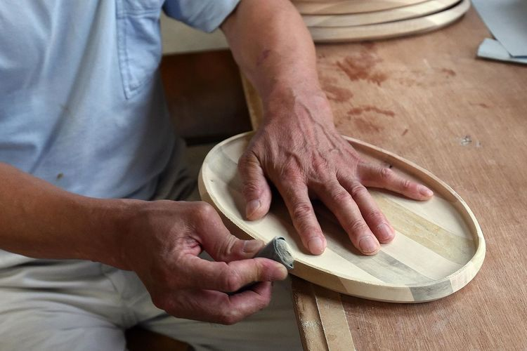 Midsection Of Craftsperson Shaping Wood At Workshop