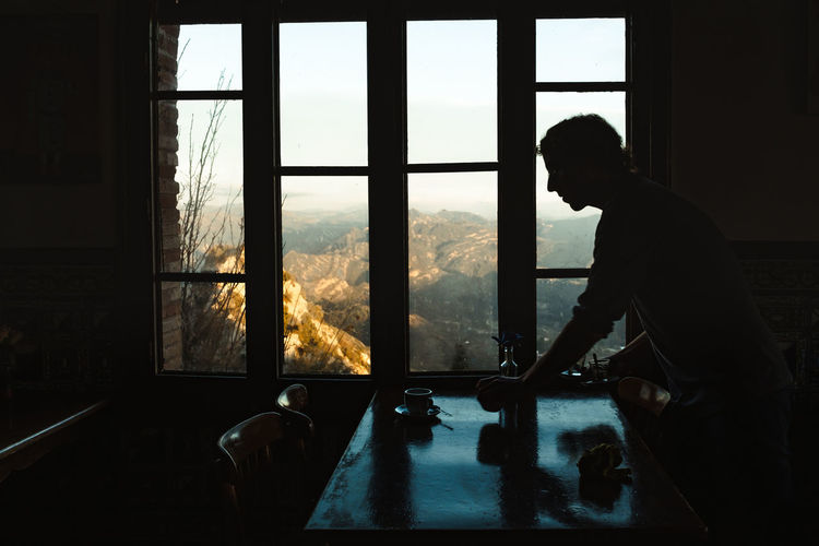Side view of silhouette man looking through window
