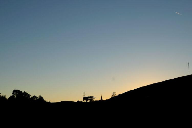 Silhouette landscape against clear blue sky