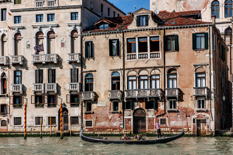 Gondola on canal by buildings in city