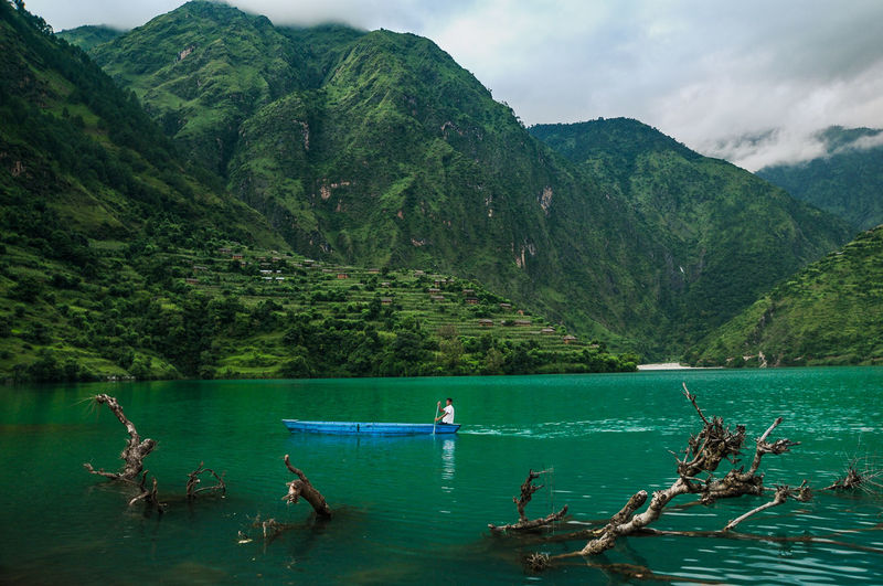 Man boating on lake against mountains