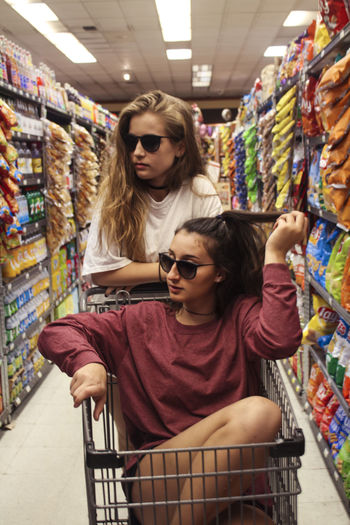 Choosing Consumerism Customer  Females Groceries Indoors  People Portrait Shelf Shopping Cart Store Sunglasses Supermarket Two People Women
