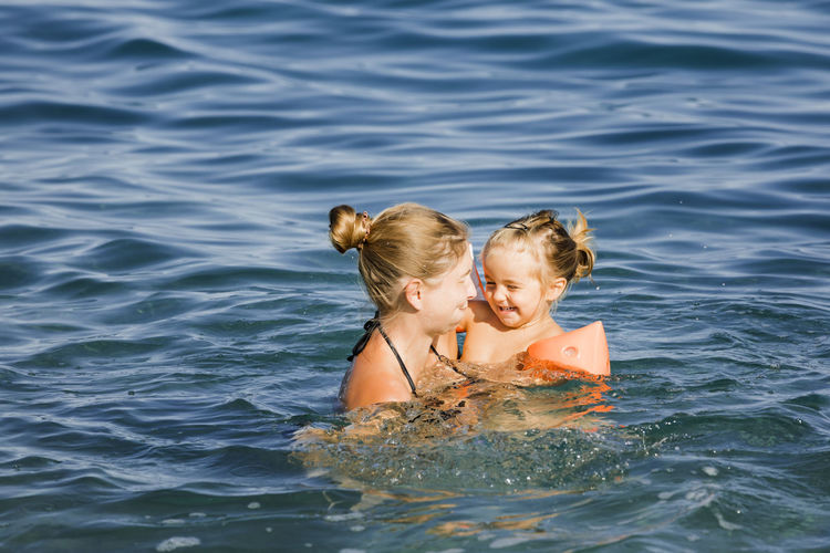 Rear view of mother with daughter in water