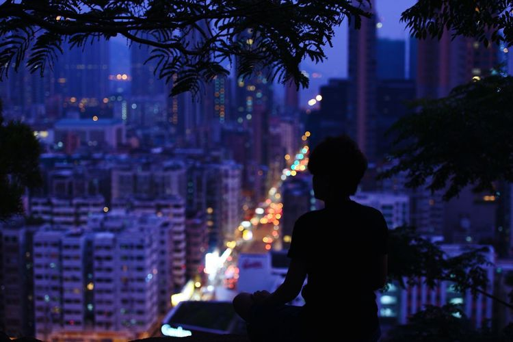 Silhouette woman overlooking illuminated city from terrace at night