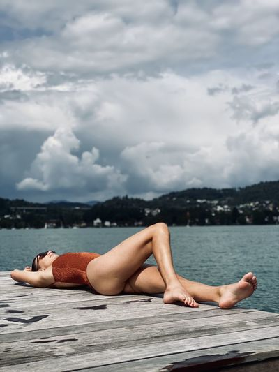 Midsection of shirtless man lying in water against sky