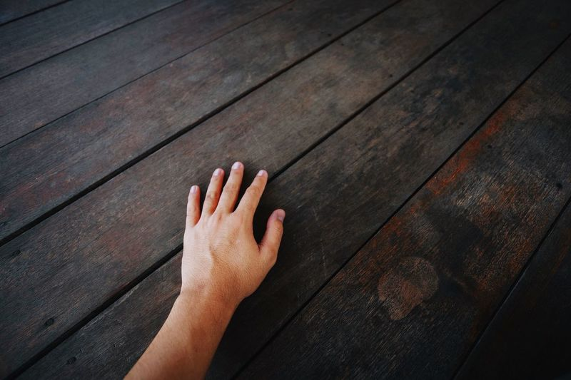 Hand over vintage wooden background Human Body Part Human Hand Hand High Angle View One Person Real People Body Part Unrecognizable Person Human Finger Flooring Leisure Activity Sunlight Close-up Personal Perspective Wood - Material Lifestyles Finger Indoors  Day