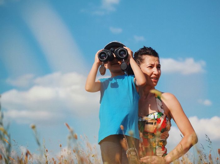 Mother with son looking through binoculars against blue sky
