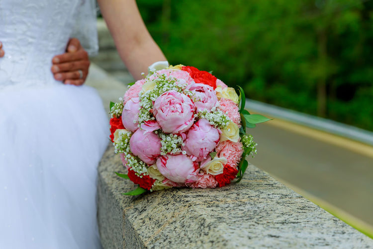 Cropped hands of groom holding bride waist by bouquet on retaining wall