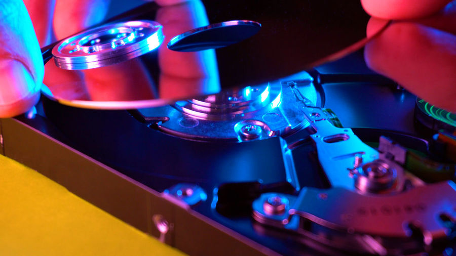 Man fixing hard drive Technology Close-up Equipment Indoors  Machinery Nightlife Nightclub Blue Turntable Record Music No People Illuminated Occupation Arts Culture And Entertainment Industry Motion Microscope Disco Dancing Clubbing Silver Colored