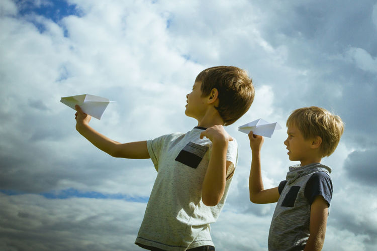 Side view of siblings playing with paper airplanes against cloudy sky