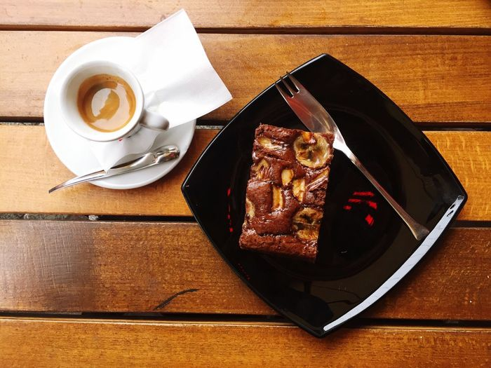 High Angle View Of Coffee And Pastry Served On Table