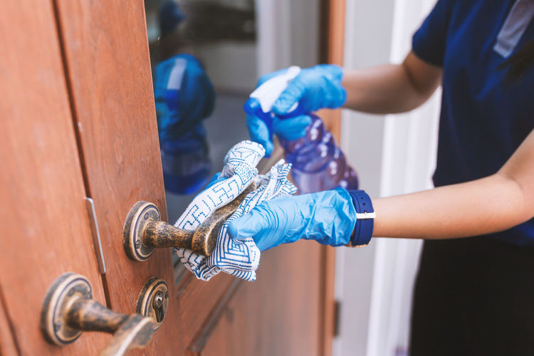 Cleaning home table sanitizing door surface with disinfectant spray bottle washing surfaces