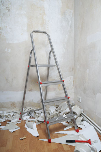 Ladder in corner of peeled wall at home