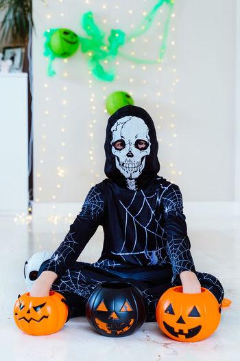 Woman wearing mask against orange wall during halloween