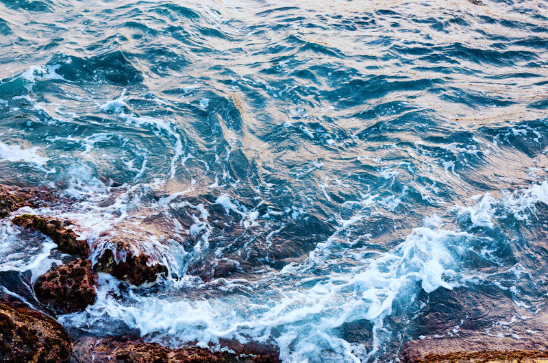Sea water hits stone beach, wave and beach, nature background concept. photo with motion blur.