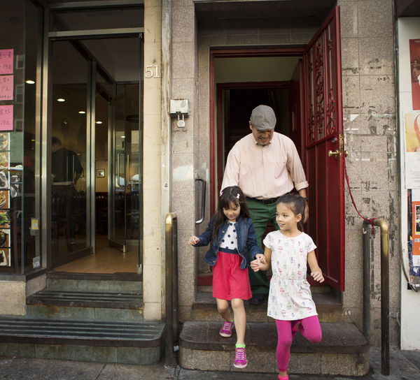 Happy grandfather with grandchildren walking out of store in city