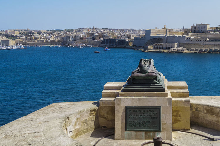 Valletta, Malta Siege War Memorial sculpture. Bronze soldier lying on a catafalque at the lower part of Saint Christopher Bastion,facing the Grand Harbour in the capital of Malta. Bronze Soldier Memorial Malta Knights Castle Malta Knights Fortifications Malta Malta Malta Grand Harbour Malta Bastioned Fort Malta Capital Maltese Fortification Maltese Historic Building Stone Sculpture Grand Harbour Valletta European Capital Of Culture 2018 Valletta Harbour, Malta Valletta Architecture Valletta,Malta War Memorial Malta Architecture Art And Craft Building Exterior Catafalque Grand Harbour Cityscape No People Sculpture Statue Valletta Water