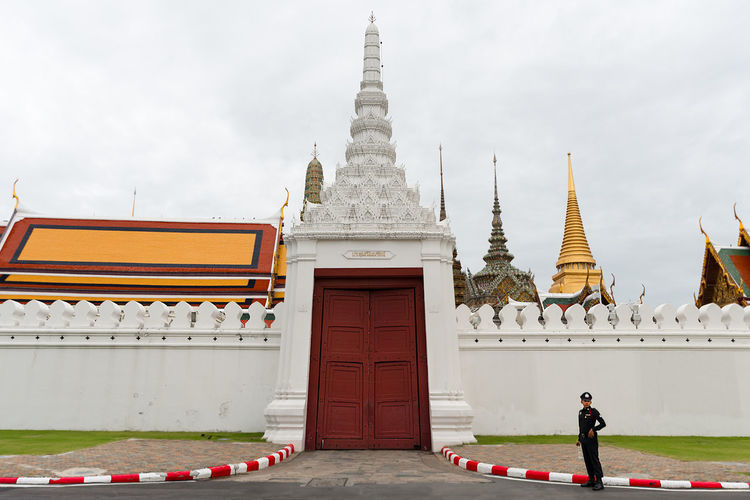 A thai Police Officer stands guard at on of the entrance gates of the Grande Palace, Bangkok, Thailand. Red Entrance Thai Police The Grand Palace Thailand Architecture Building Exterior Built Structure Day Men Outdoors Pagoda People Place Of Worship Police Uniform Real People Red Gate Religion Sky Travel Destinations