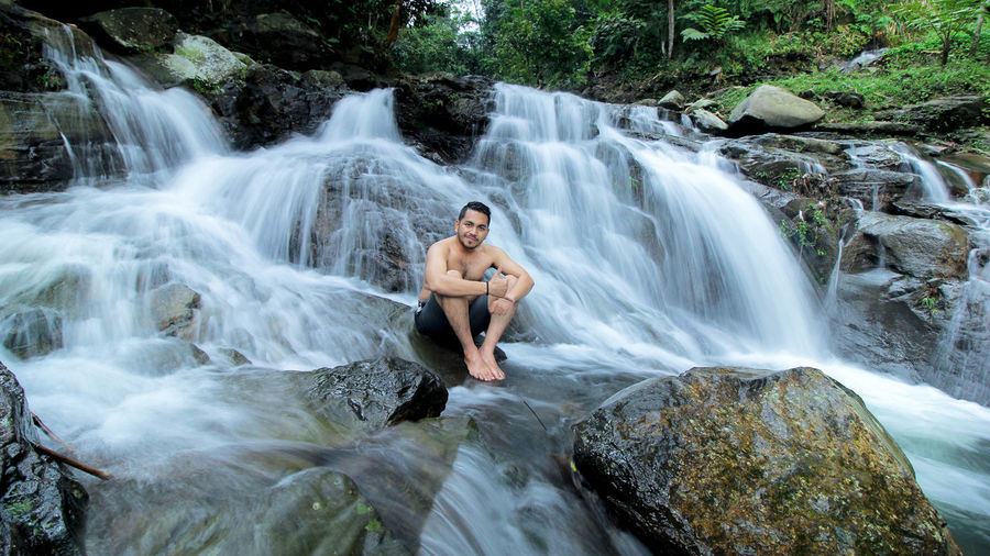 Full length of man waterfall on rock in forest
