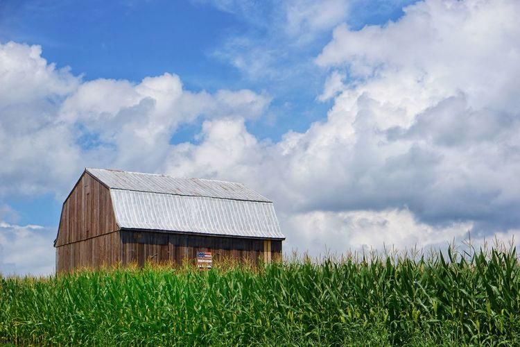 Barn on field against cloudy sky