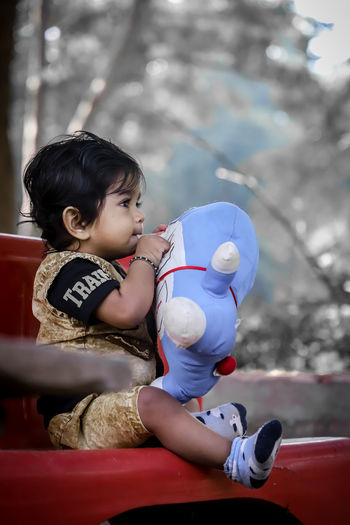 Cute boy playing with toy while sitting on bench