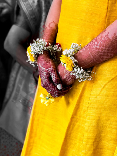 Close-up of woman holding yellow flowers
