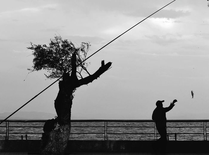 Silhouette Men Fishing At Sea Against Sky