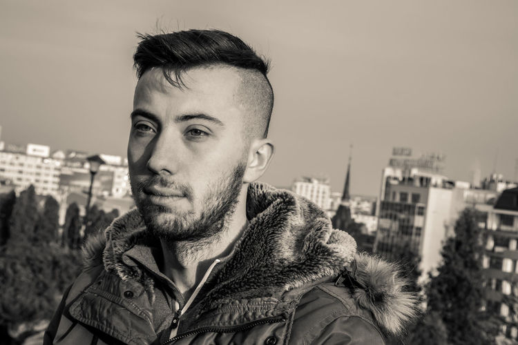 Young Man In Fur Coat Looking Away Against Cityscape