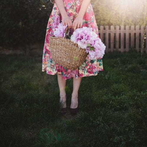 Low section of woman standing in the garden with a basket full of pink flowers