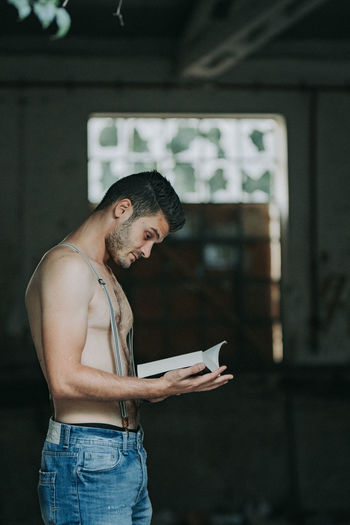 Side view of young man reading book indoors