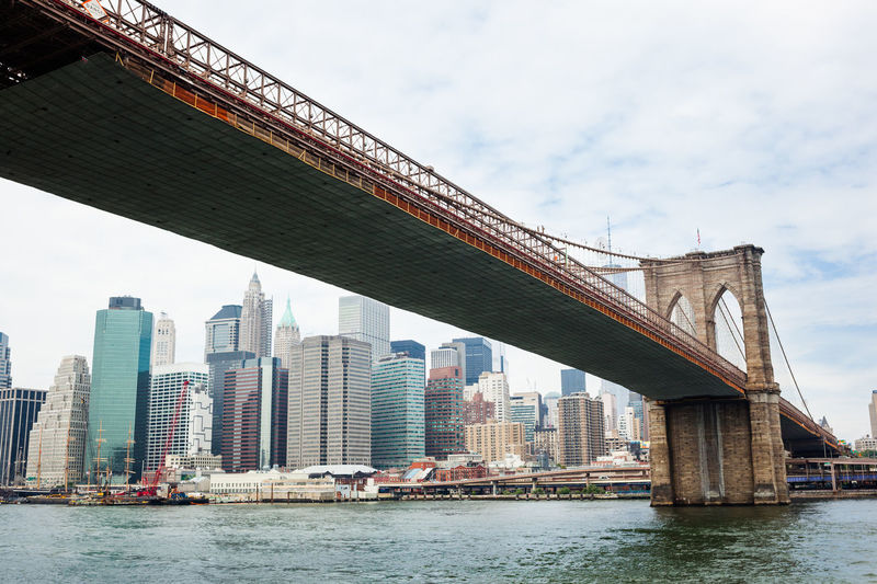 Low angle view of brooklyn bridge over river in city against sky